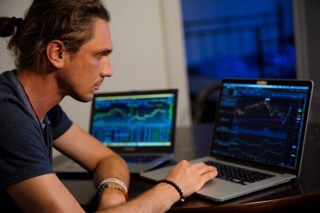 chico trabajando en trading con su ordenador