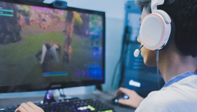 chico jugando al ordenador con auriculares gaming