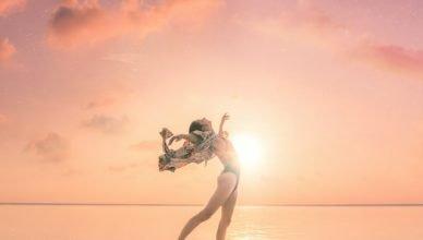 chica saltando en la playa feliz ante el atardecer