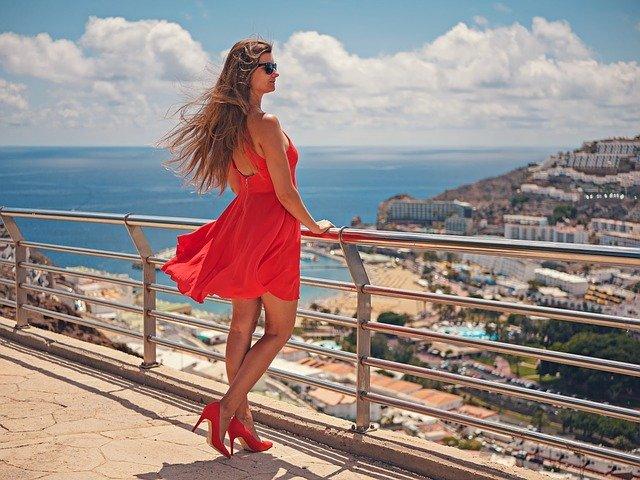 chica con un vestido y zapatos rojos anaranjados mirando el infinito