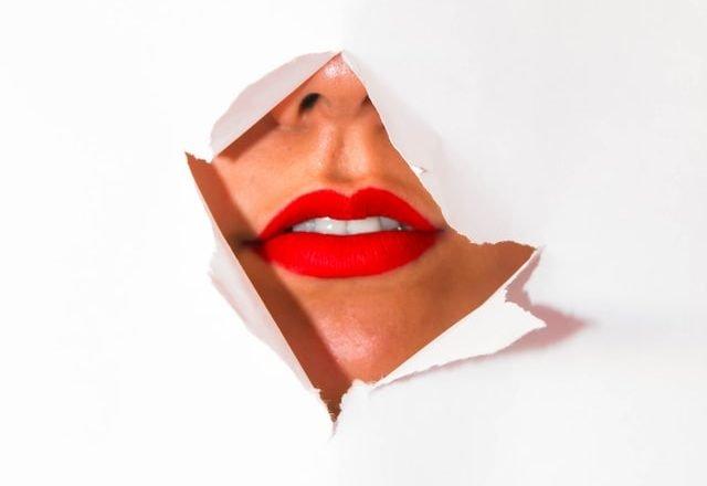 labios de una mujer que esconde el pelo en la boca que le creció