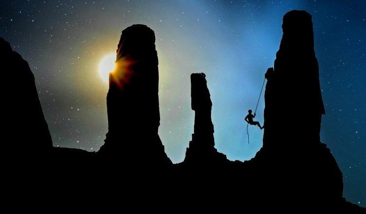 persona escalando una piedra en la noche
