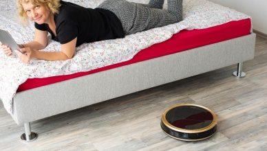 mujer tumbada en la cama mientras su robot limpia
