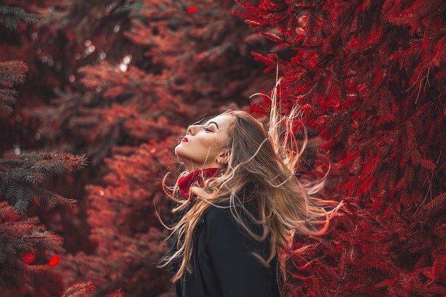 chica feliz respirando el aire de un bosque