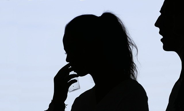 silueta de una chica con coleta cogiendo un baso de agua y detrás suyo, silueta de un hombre con la boca abierta
