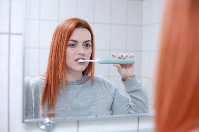 chica limpiándose los dientes con un cepillo eléctrico