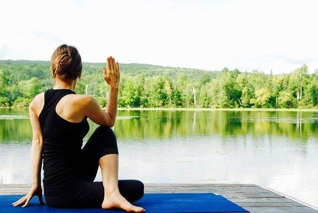 Mujer practicando yoga delante de un lago