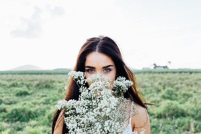 mujer tapandose parte de la cara con flores