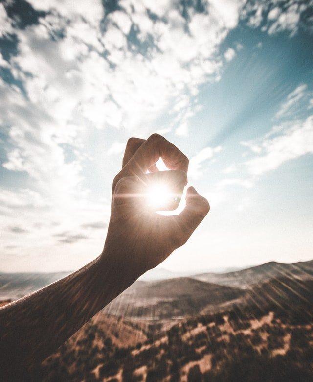 mano intentando capturar el sol