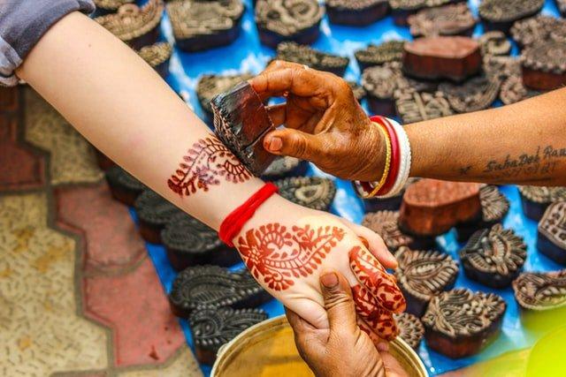 mujer tattuando a una persona con henna
