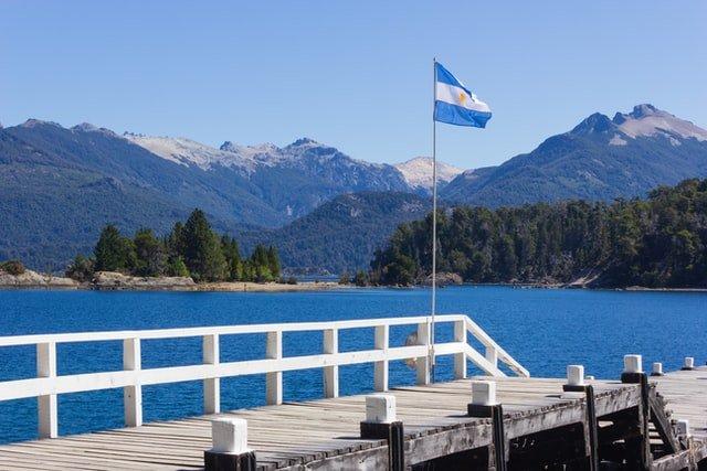 paisaje de lago y montaña con la bandera de Argentina