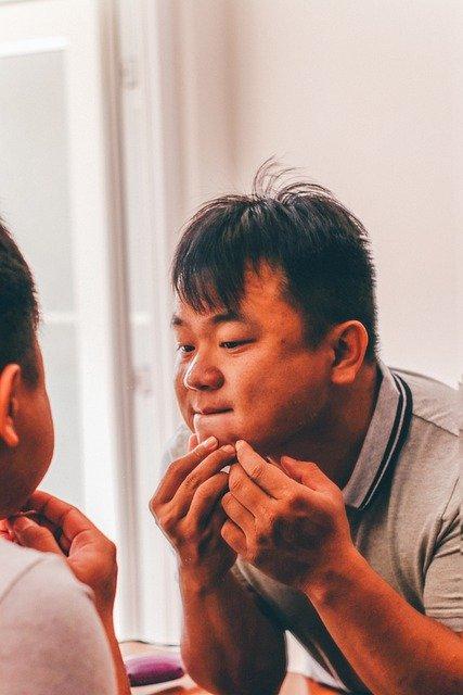 hombre pinchandose los granos de su cara