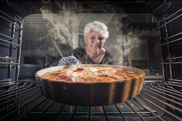 mujer sacando su plato cocinado del horno