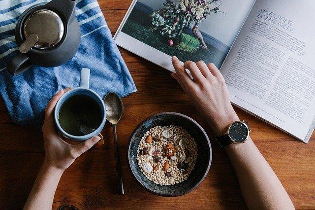 persona tomándose un desayuno mientras lee