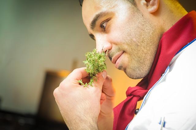 chef oliendo las hierbas que quiere poner en su sopa