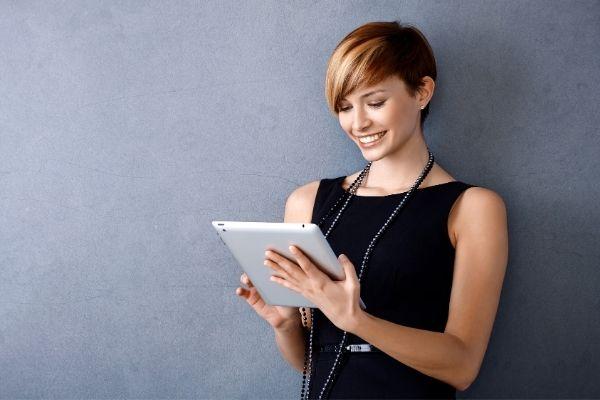 mujer sonriendo mirando su tablet