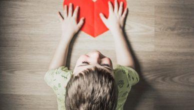 niño con un corazón de papel en la mano