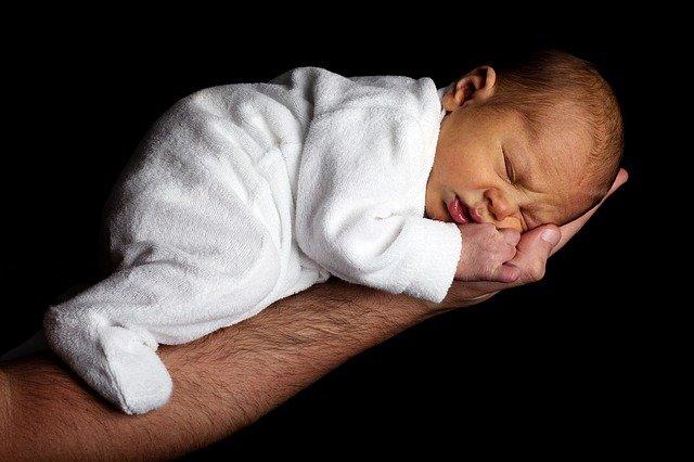 niño pequeño cogido en una sola mano