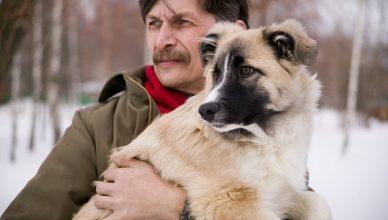 hombre con su perro cogido en brazos