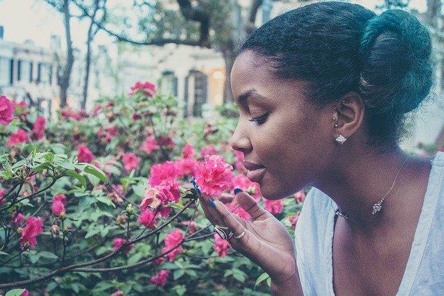 mujer que decide ser feliz oliendo flores