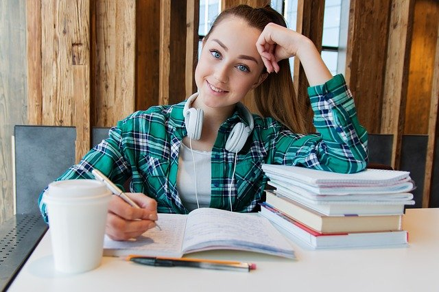 chica utiliza auriculares al estudiar para aumentar su concentración