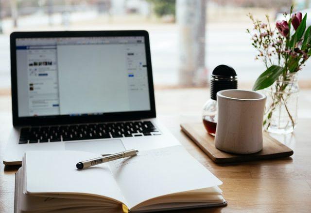 ordenador y libreta encima de la mesa